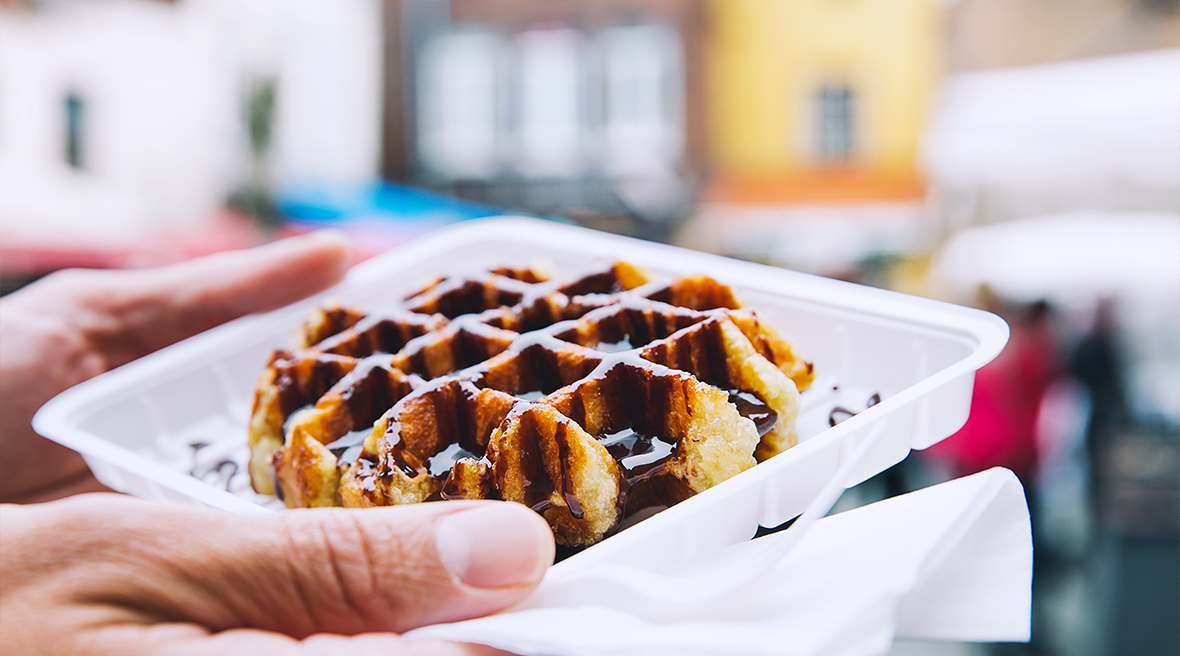 A Belgian waffle covered in chocolate sauce