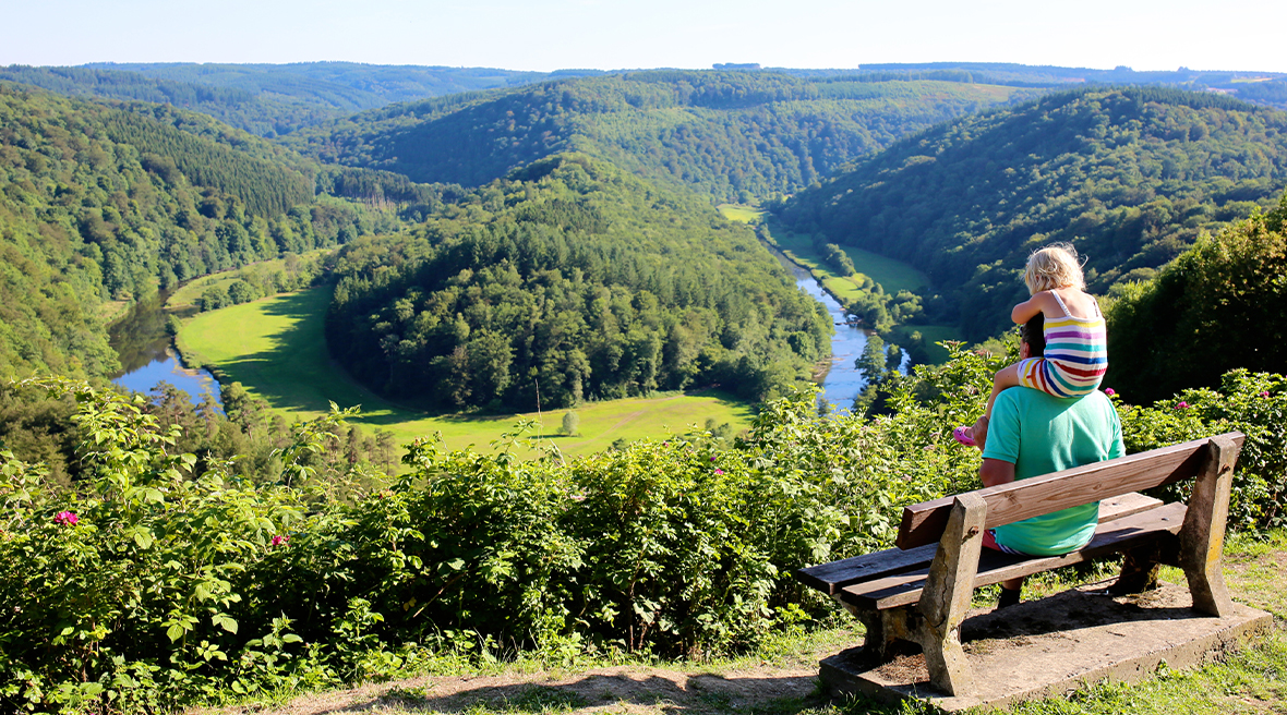Father and child look over woodland and a river in the Ardennes