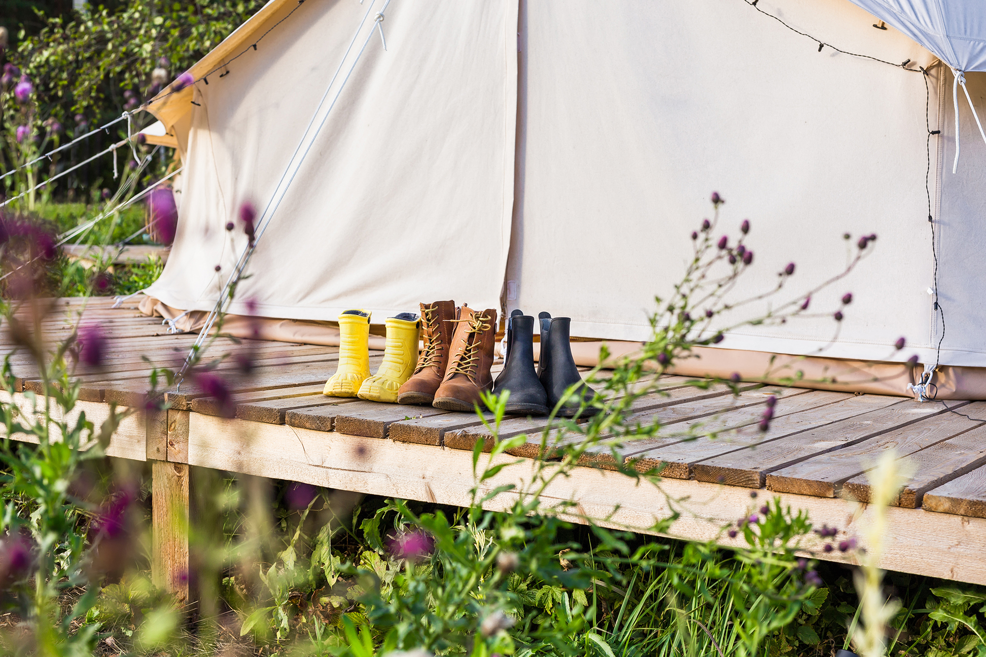 Bell tent with decking with a row of outdoor boots and bright yellow wellies lined up in front of the tent entrance