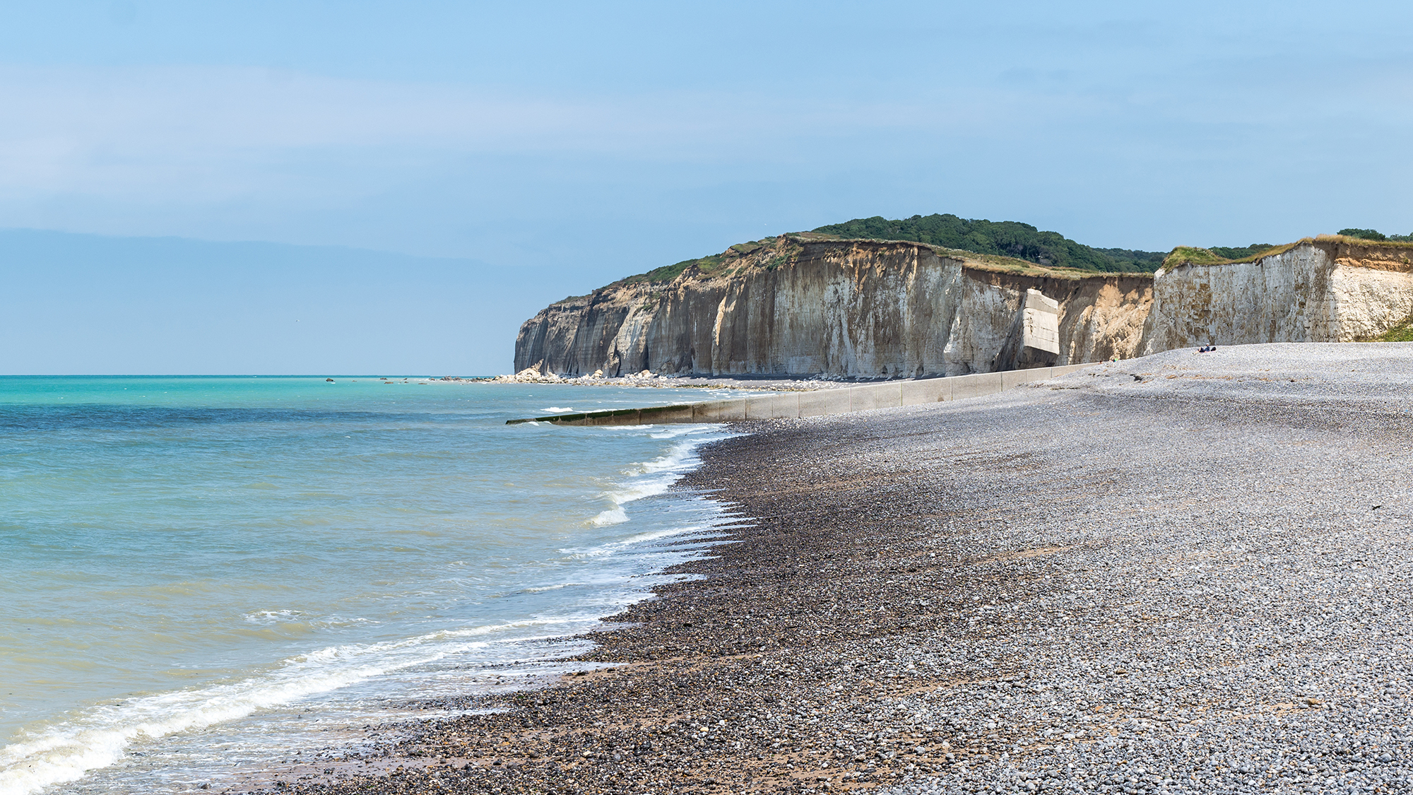 Normandy pebbled beach with clear blue waves washing onto the shore with green cliff tops in the background