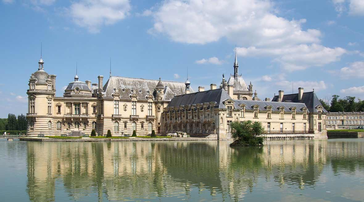 White brick French castle with turrets on a body of water under a blue sky