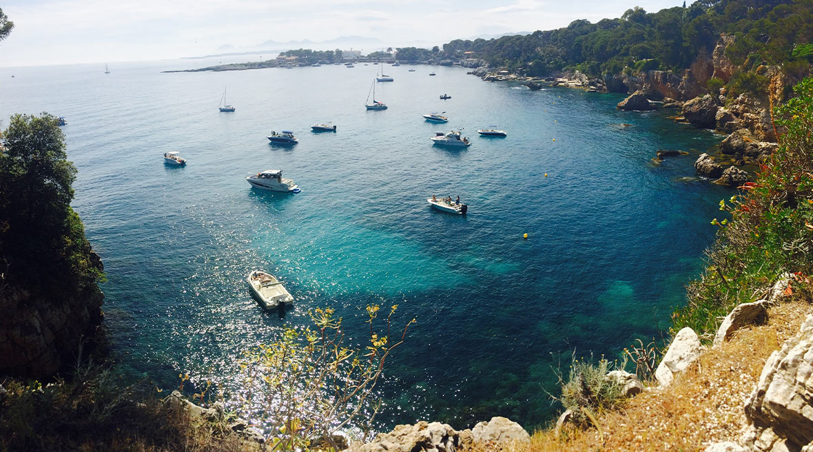 Boats dotted across blue water in a cove off the French coast