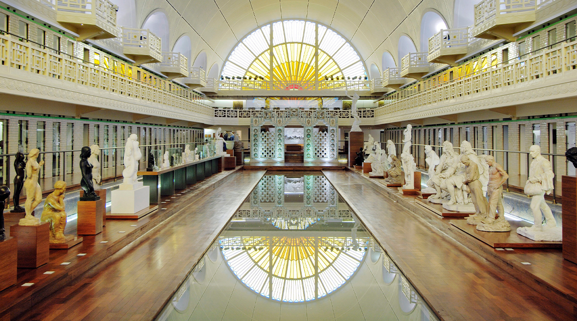 Art deco-esque stained glass window overlooking the swimming pool, with statues on both sides, in the Musée d'Art et d'Industrie, Roubaix, France