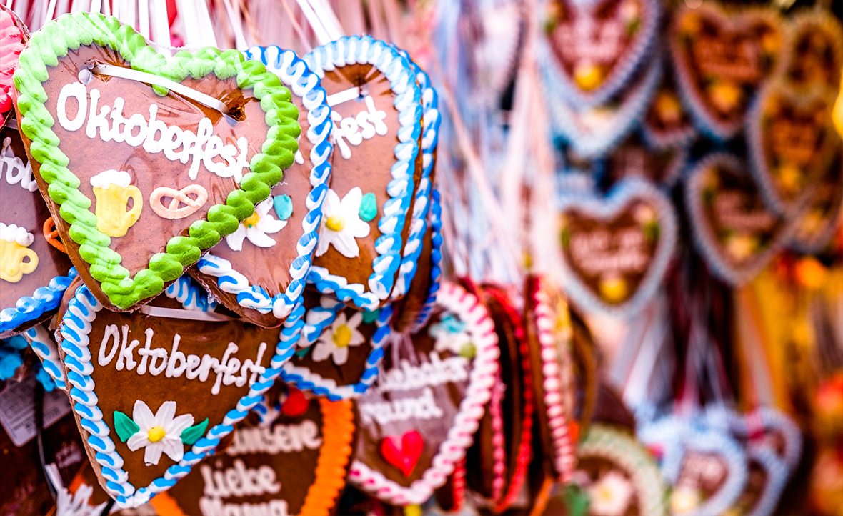 Heart shaped gingerbread hanging from ribbons with Oktoberfest written in colourful icing