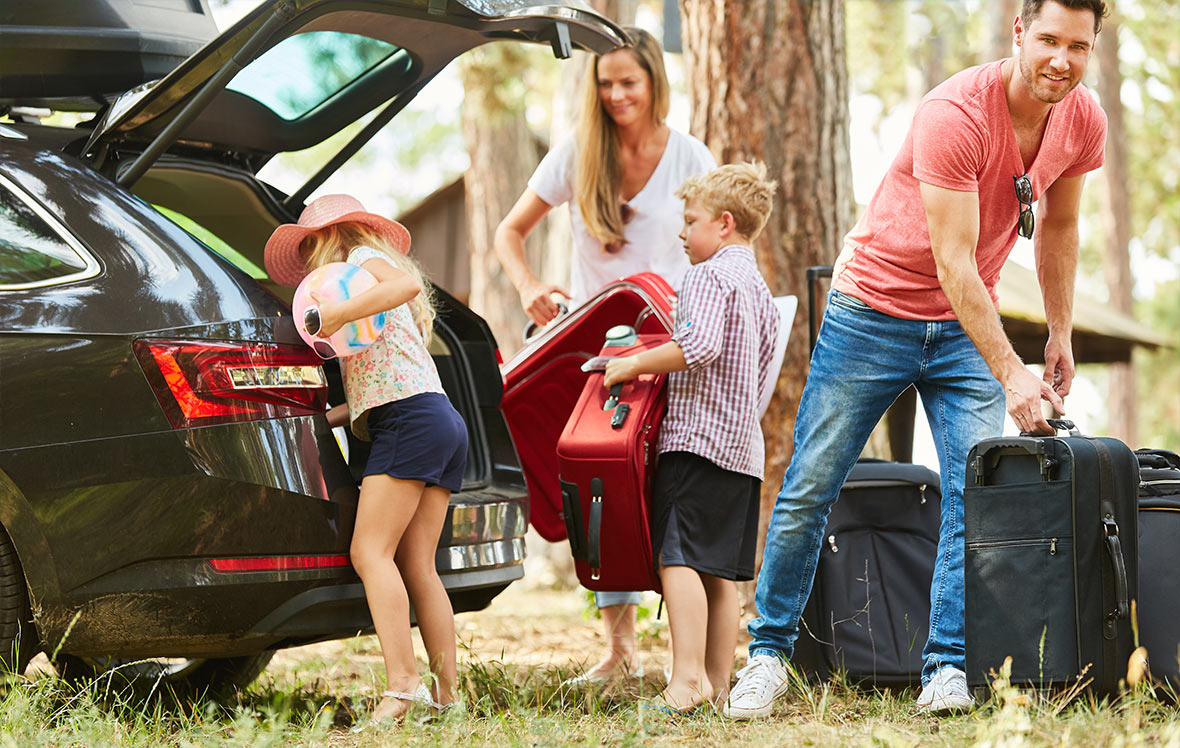 family dressed for summer packing car with suitcases for a holiday