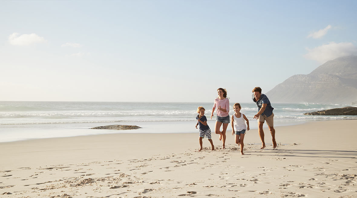 family of four running across a sunny beach in the sun