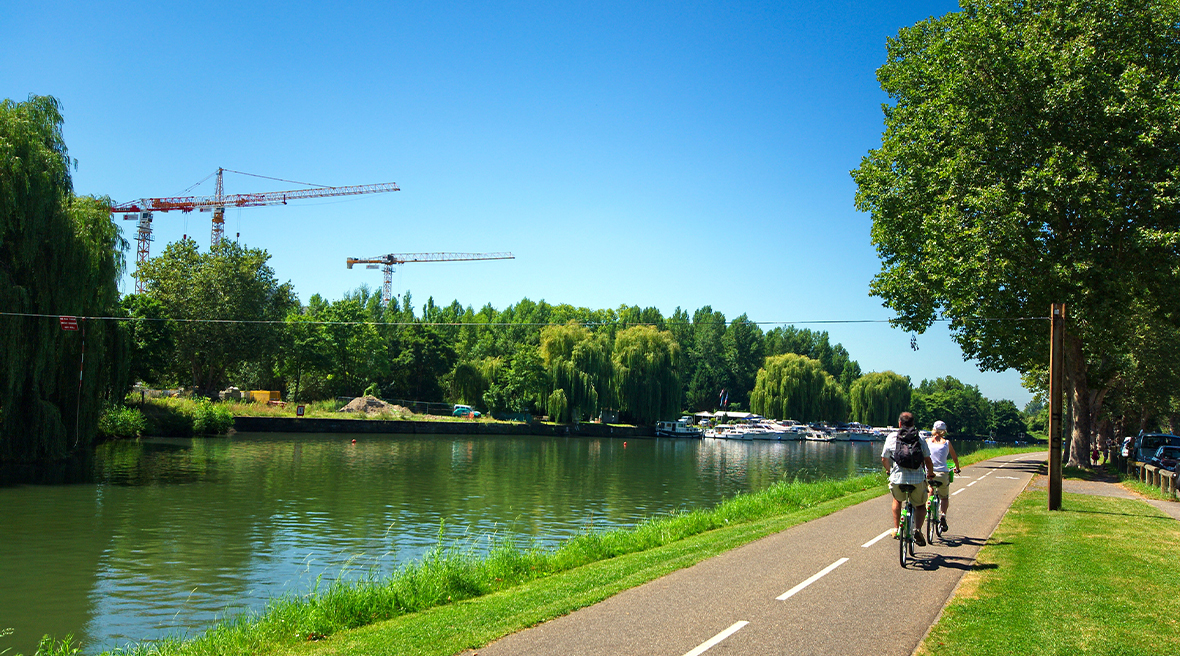 Two cyclists riding along a canal