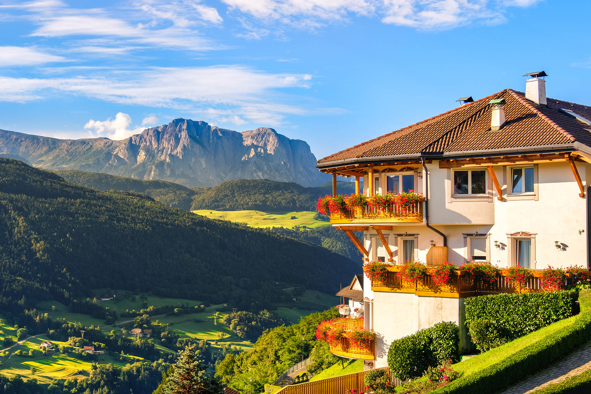 Multistory building with balcony overlooks a sunny Italian Dolomites, with lush green surroundings.