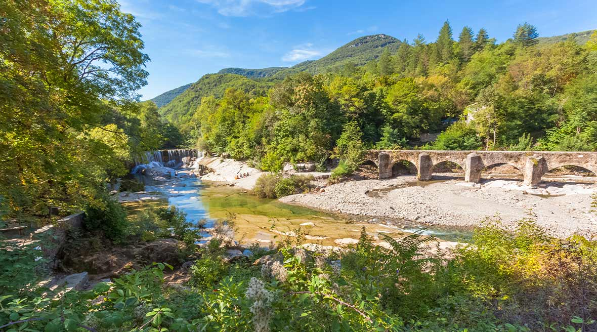 stone bridge on a pebbled beach next to a river surrounded by trees and hills under a sunny sky
