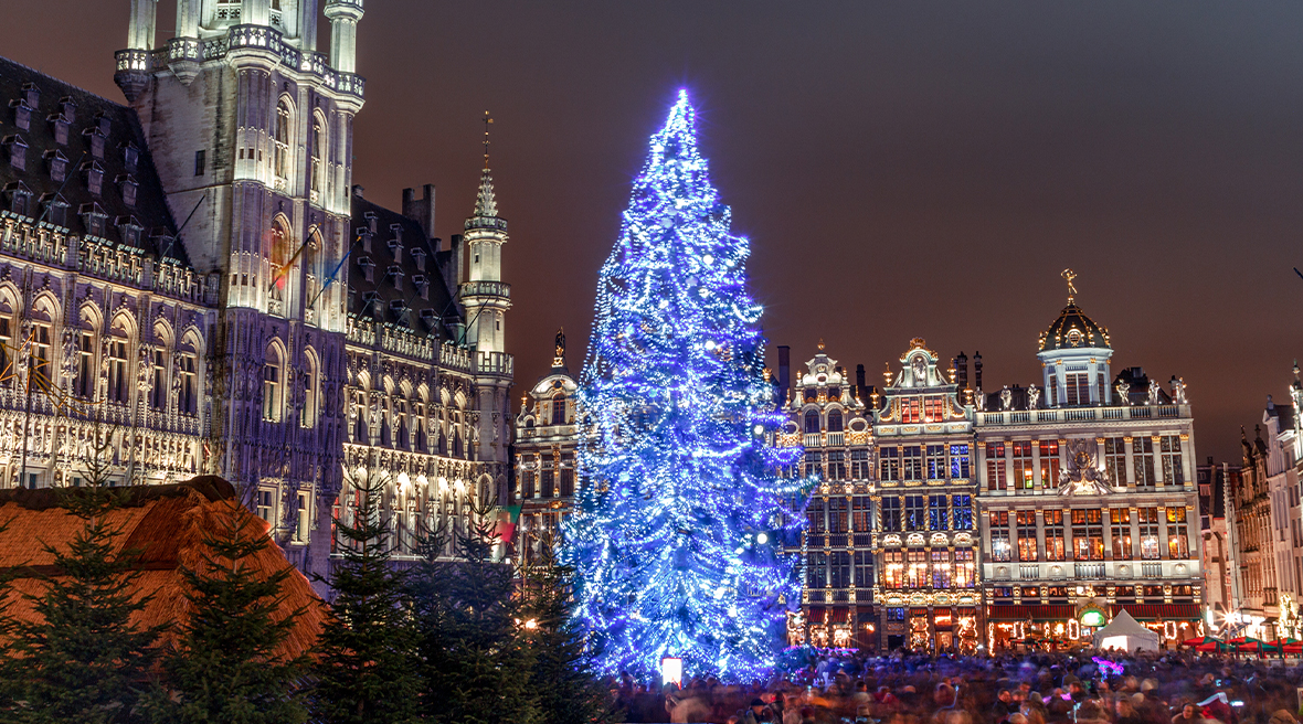A Christmas tree lit up with blue lights surrounded by tall Grand buildings and a crowd below