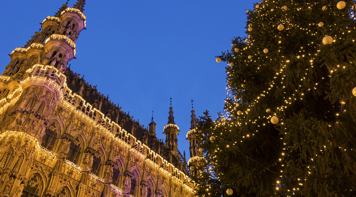 A tall Christmas tree decorated in gold lights and baubles next to Leuven City Hall which is illuminated by lights