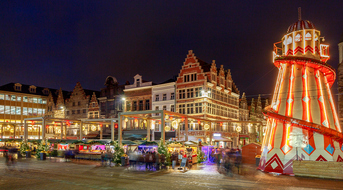 Buildings at night with Christmas market stalls and an amusement ride