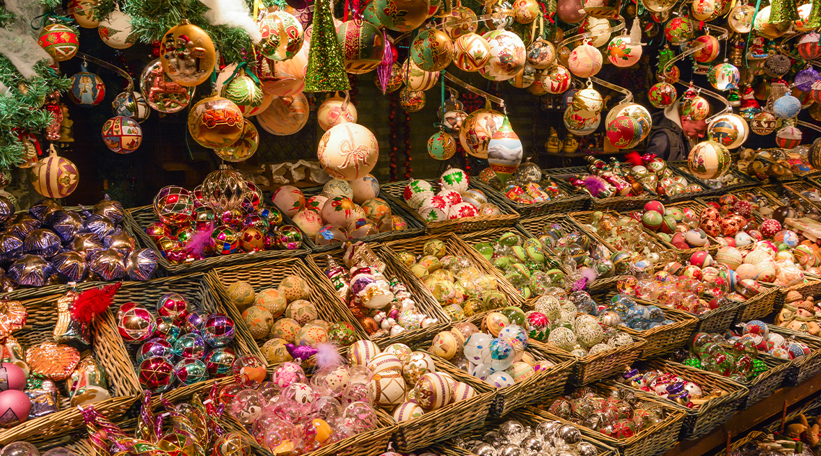 Christmas baubles in baskets and hanging from ceiling of market stall