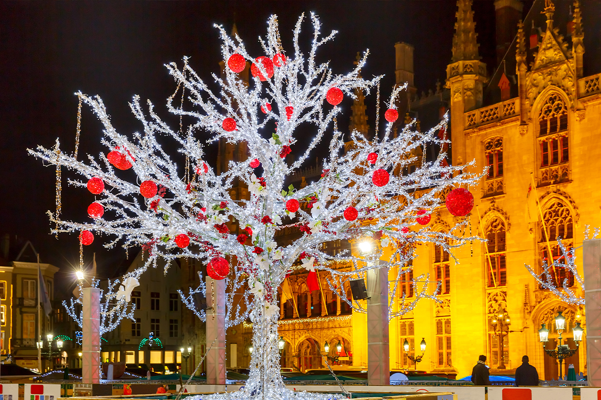 A Christmas tree made of white lights decorated with large red baubles stood in front of buildings