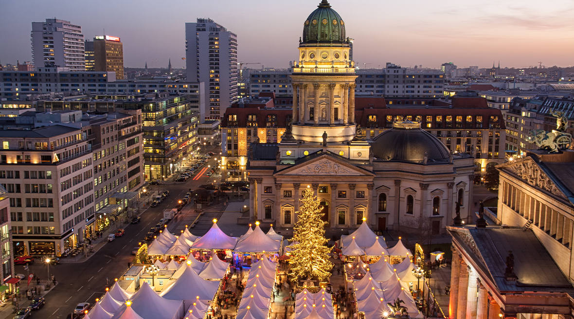Berlin city skyline with lit up Christmas tree and market stalls at night