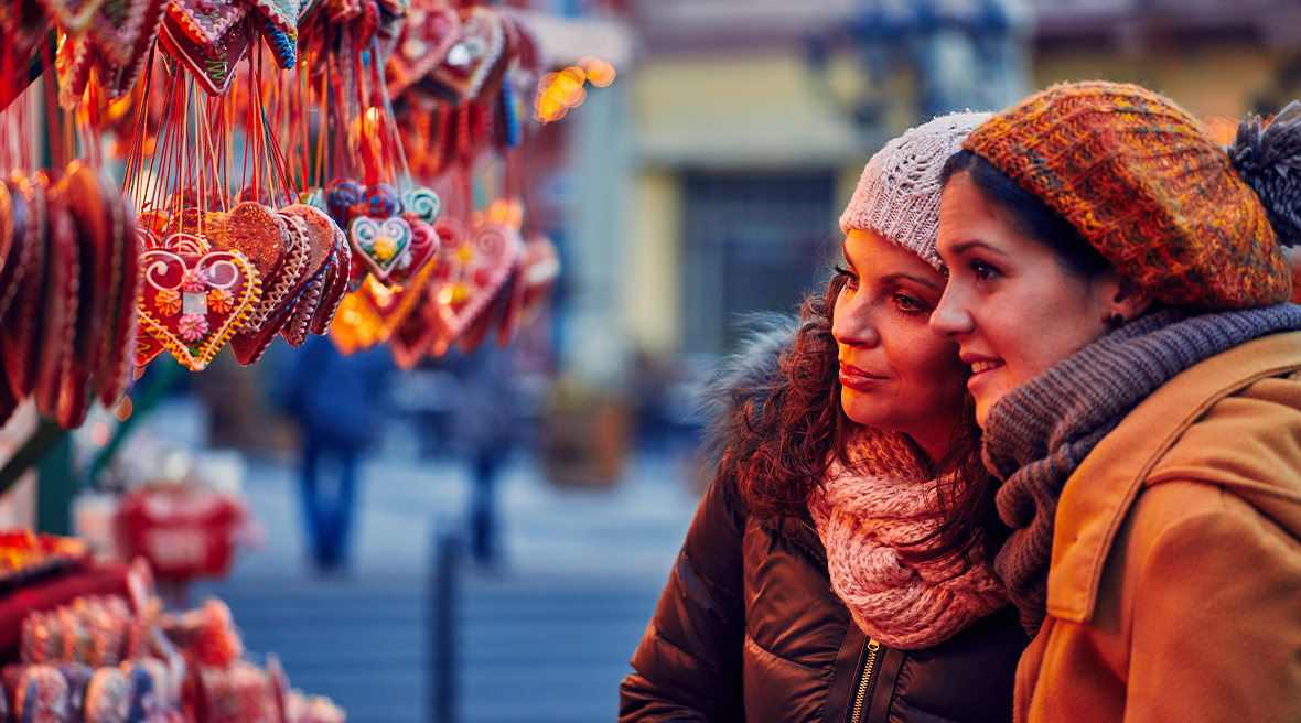 two women in coats and hats looking at beautiful Christmas decorations hanging from market stall