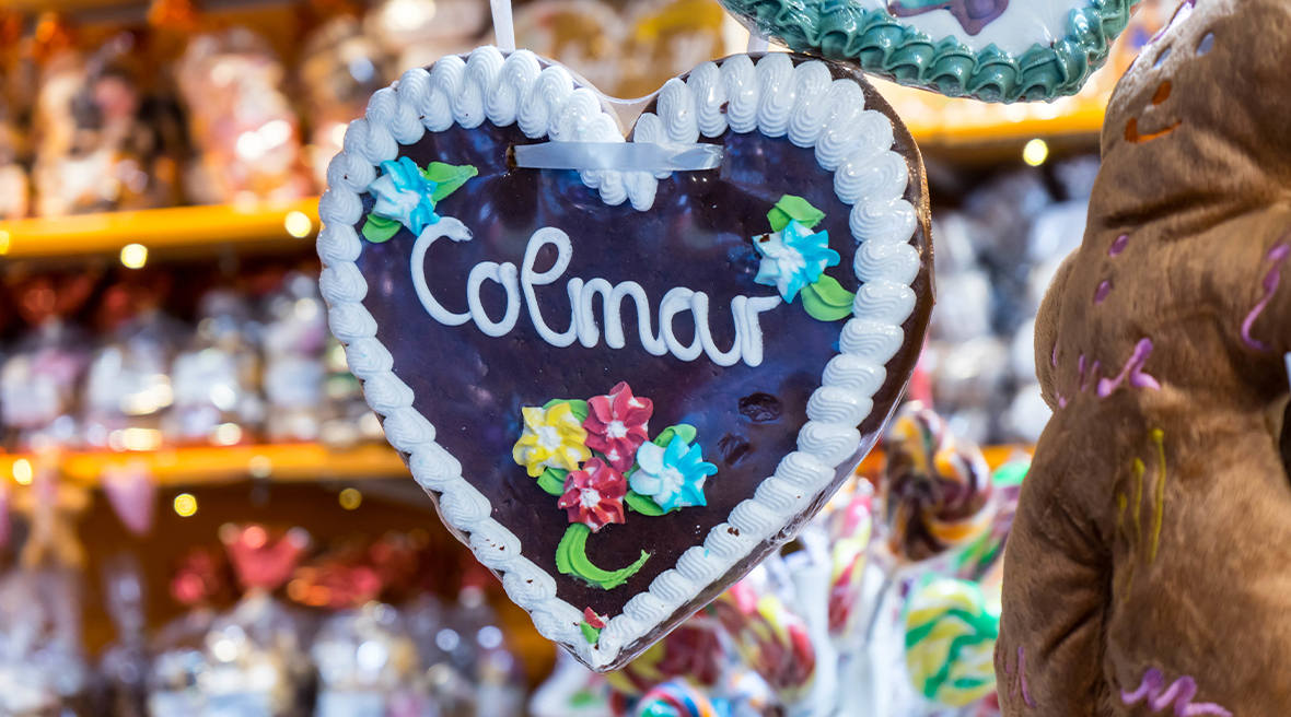 Decorated heart shaped biscuit with Colmar written in icing across middle