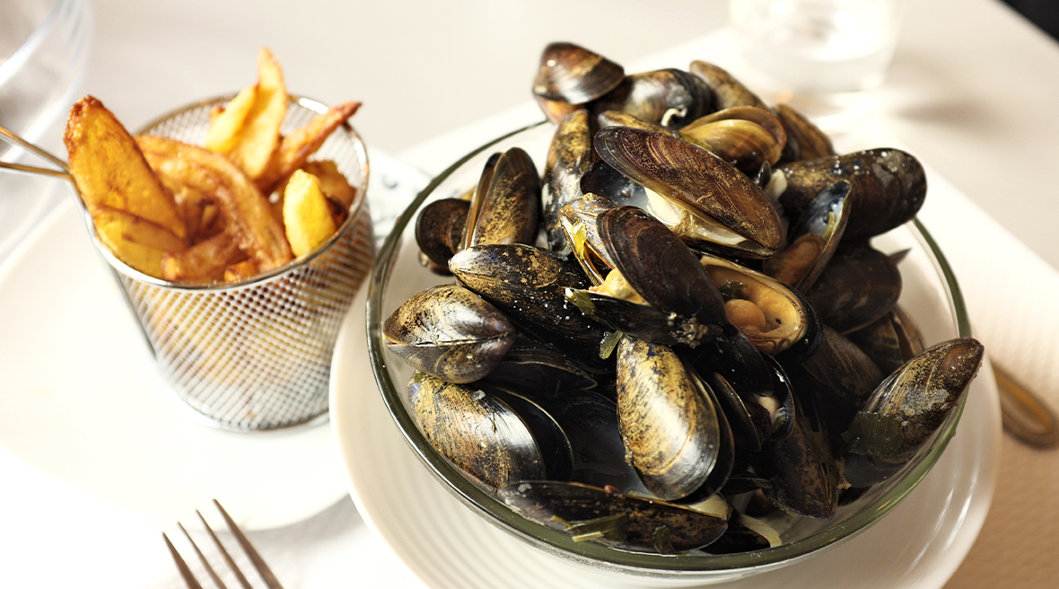 Bowl of mussels next to a metal mesh container of chips at a restaurant table