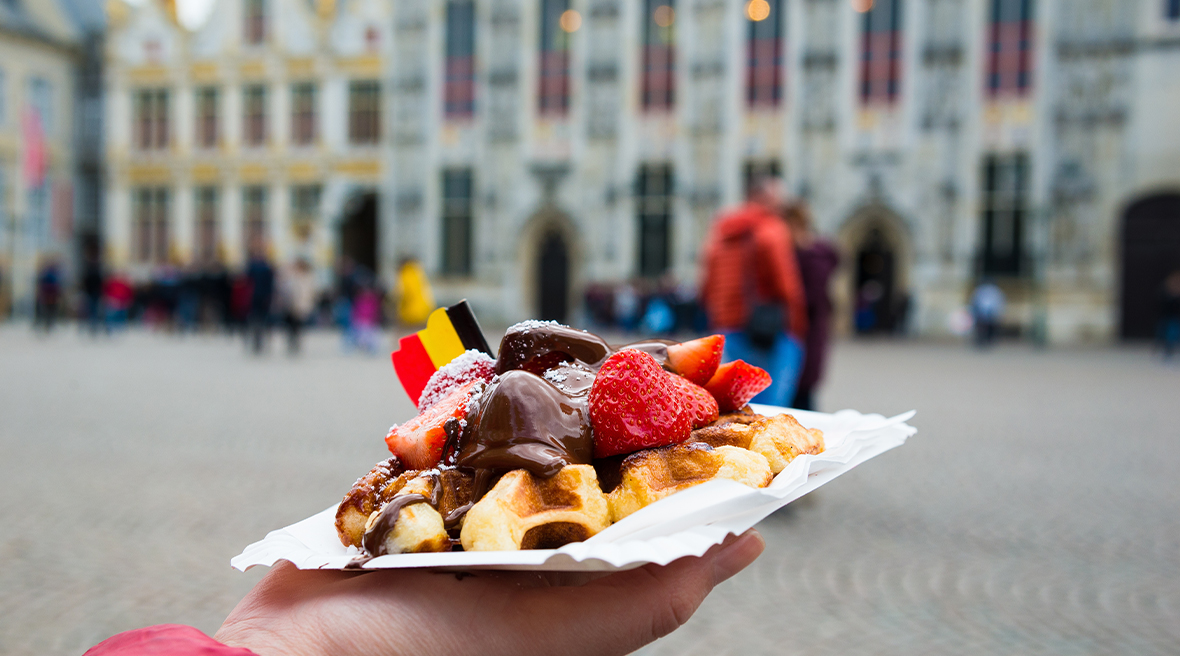 Belgium waffle with chocolate sauce and strawberries with a Belgian flag with Bruges city in the background