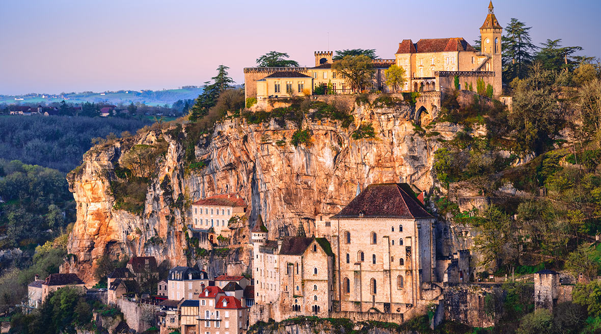 A pretty French village set back into a cliff edge with a lush green valley surrounding it