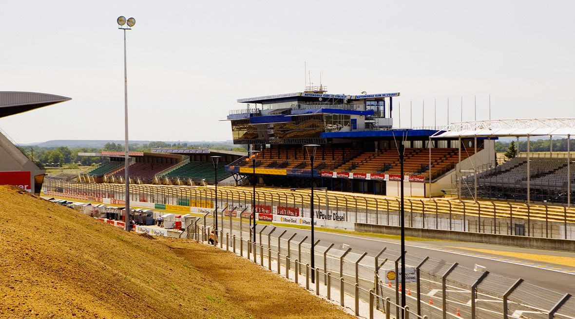 fenced multicoloured seating stand areas overlooking a racing track