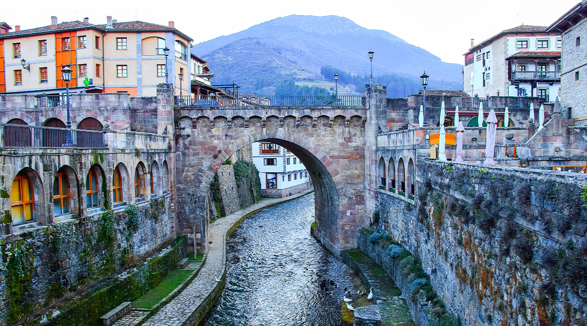 Cantabria is filled with traditional towns like Potes -tag: river running through an old Spanish town with mountains in the distance