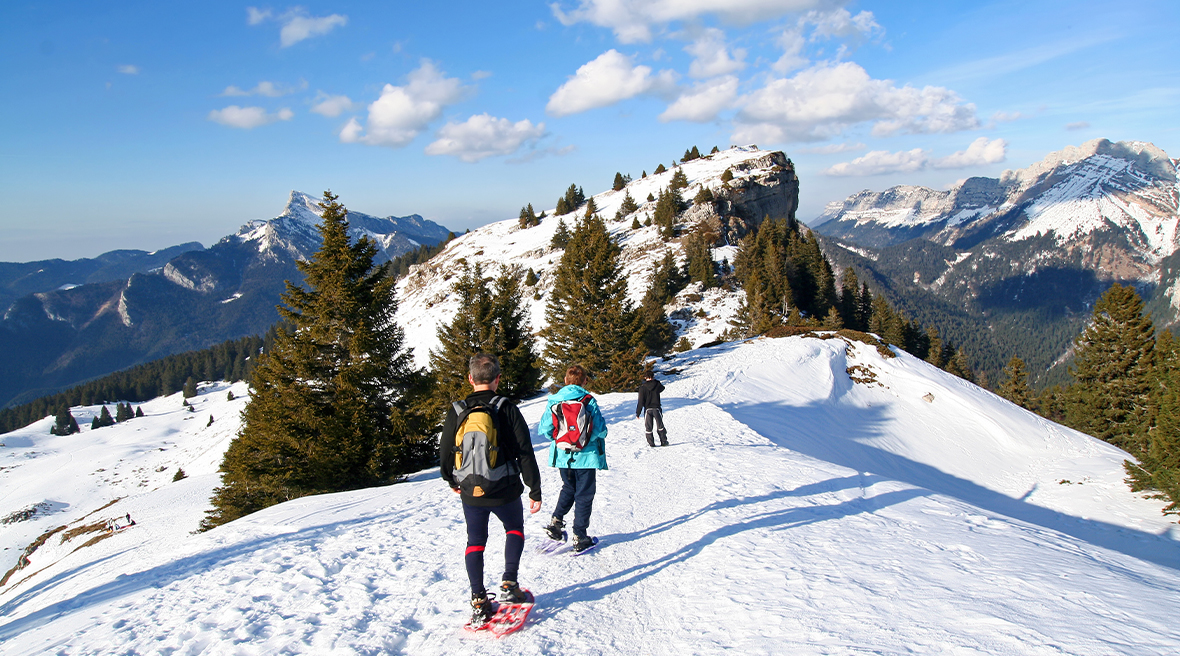Group of friends snowshoeing over a mountain range covered in fluffy white snow