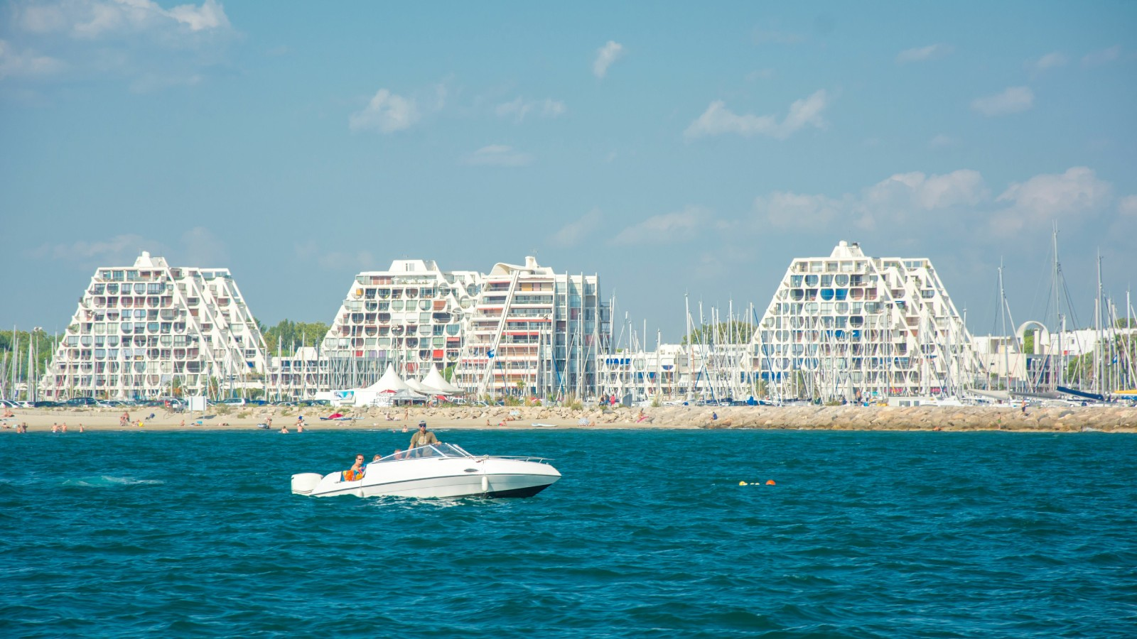 White triangular shaped buildings sitting on a sandy beach with blue skies