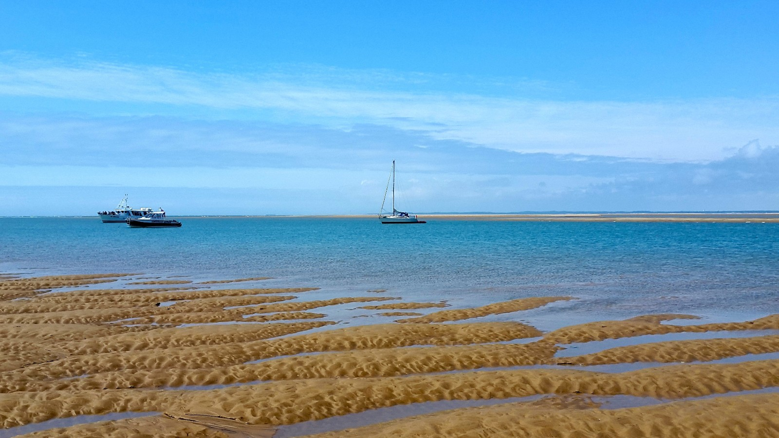 tide out on a golden sandy beach with a boat on the blue water