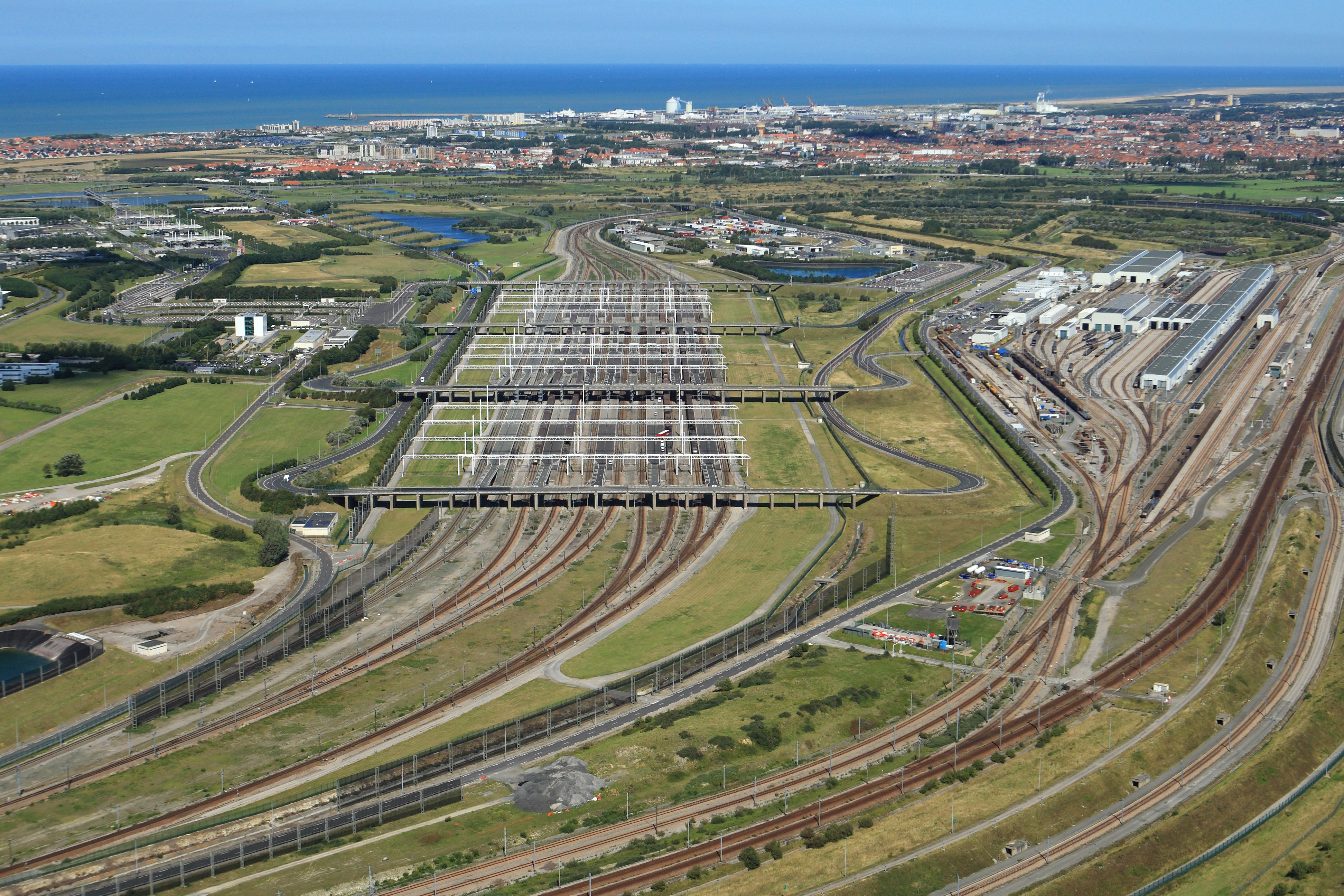 A panoramic view of Eurotunnel Le Shuttle train tracks stretching over green and brown fields dotted with buildings running under a blue bridge with blue water in the distance