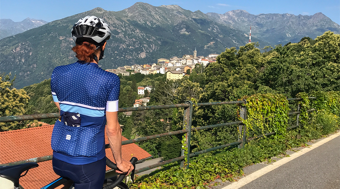 A woman in blue cycling clothing with a white helmet stopping on her bicycle to take in view of mountains and picturesque village