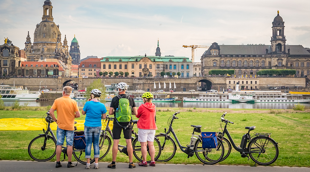 Group of four cycling friends dressed in cycling gear looking at a view of Dresden over a river
